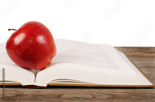 Open book with apple isolated on white background