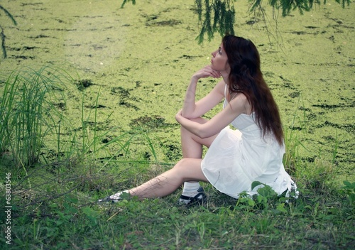 girl on bank of pond