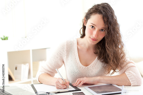Young attractive business woman copying data on paper
