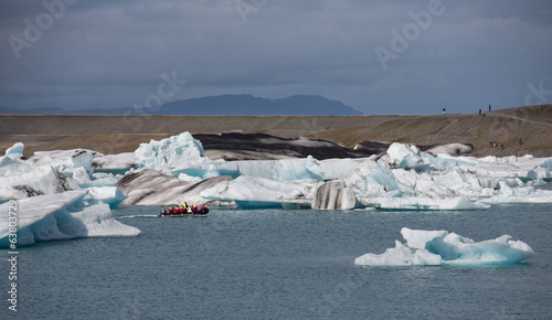 blue icebergs, lagoon and tourist boat