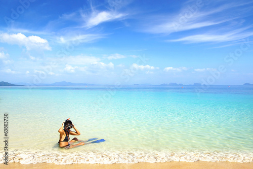 Woman on beach with snorkeling mask and fins.