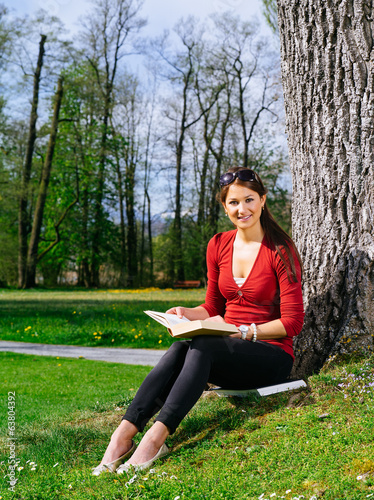 Woman reading and sitting against a tree