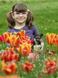 little girl with puppy in the tulip flower garden