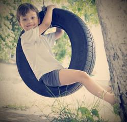 happy boy on swing outdoors