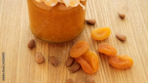 Dried apricot with nuts and jam rotate on wood plate, left
