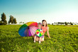 Cute little girl with mother  rainbow umbrella holding  in the p