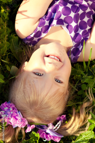 Cute little girl lying on the grass in the park. Smiling nice ch