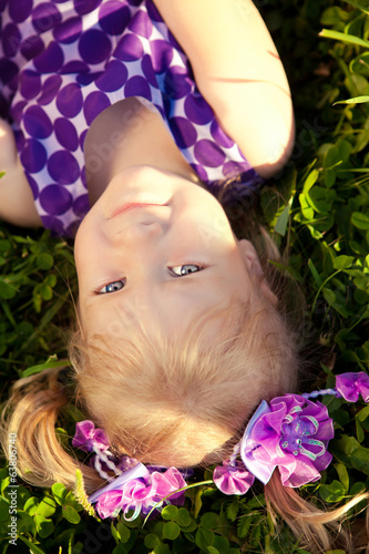 Beautiful little girl lying on the grass in the park. Smiling ch