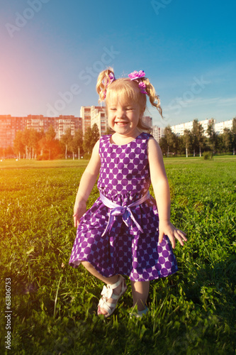 Beautiful little girl on the grass in the park. Smiling child on