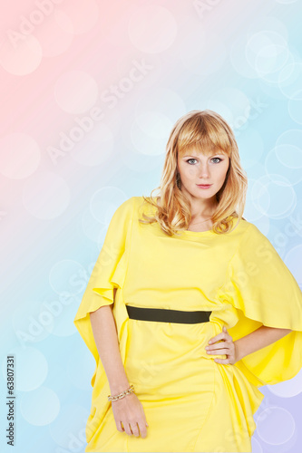 beautiful young blond woman in yellow dress on spring background