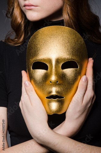 Redhead woman in hat  iwith mask in hypocrisy consept against gr