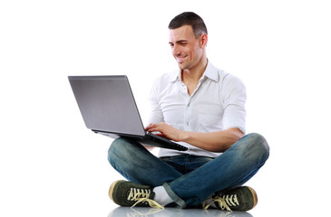 Smiling man sitting at the floor with laptop