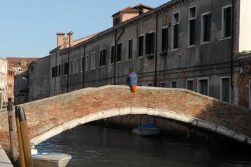 Assis sur le pont Widmann à Venise