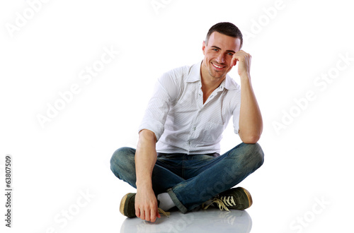 Handsome happy man sitting at the floor over white background