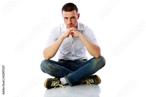 Confident man sitting at the floor over white background