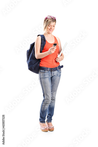 Female holding a ruler and looking at cell phone