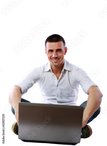 Cheerful man sitting at the floor with laptop