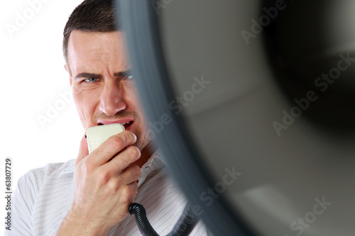 Closeup portrait of a man roaring loudly into megaphone