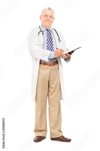 Mature male doctor writing on clipboard
