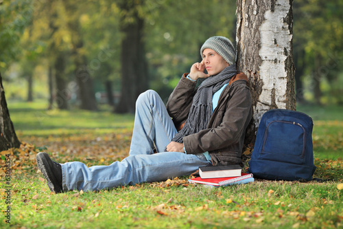 Male student thinking, seated by a tree in park