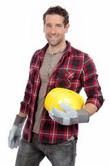 Handwerker mit Arbeitshandschuhen und Helm in der Hand