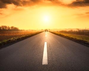 Driving on asphalt road towards the rising sun