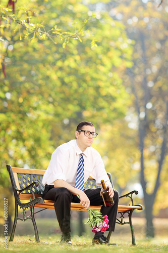 Sad man drinking alcohol and holding flowers in park