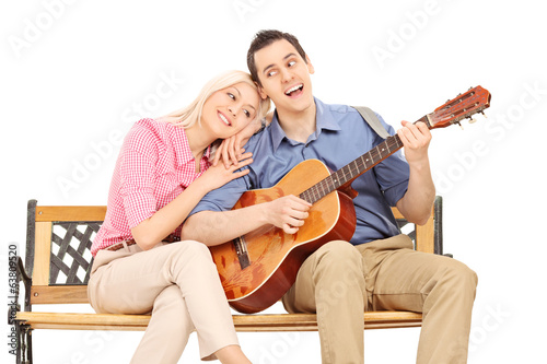 Young guy playing guitar to his girlfriend