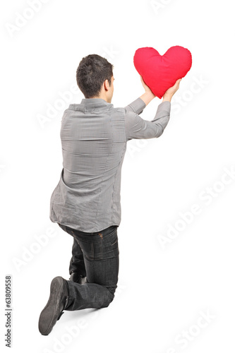Young man holding a red heart rear view