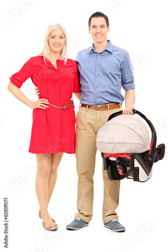Young parents holding a baby stroller