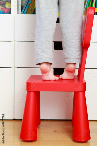 child feet on baby chair, kids home safety concept