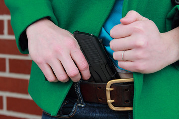Woman Pulling Concealed Weapon From Pants