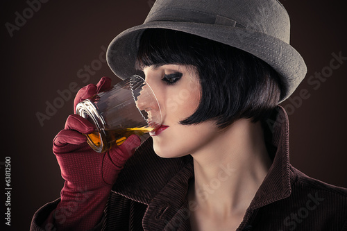 attractive woman detective drinking whiskey from a glass