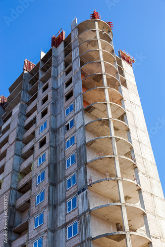 Tall building under construction against a blue sky