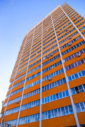 Tall apartment building on blue sky background