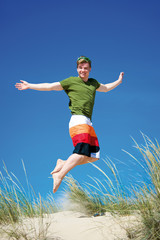 Teenager springt auf Sanddüne