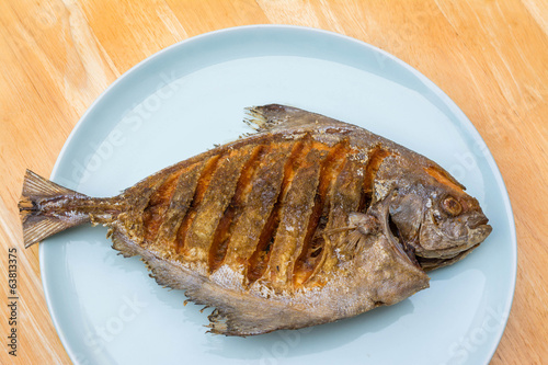 Asian style deep fried pomfret on dish in wooden table backgroun
