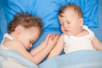 Adorable little brothers sleeping together in bed