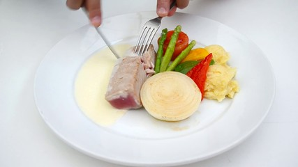 A person eating tuna steak as main dish.