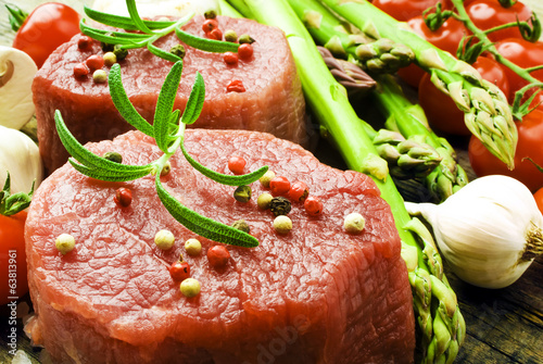 Raw Steak with green asparagus on wooden board