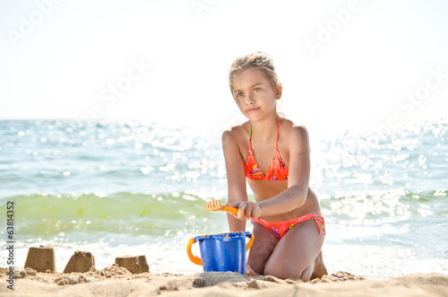 Kid on beach in sand playing. girl in an orange swimsuit.