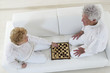 Top view of a senior couple sitting on floor playing chess