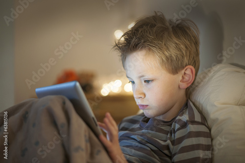 little boy at expressive face using a digital tablet in bed