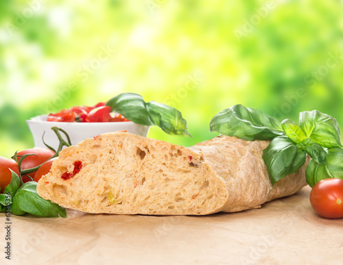 Italian bread  ciabatta with tomatoes and basil  in green garden