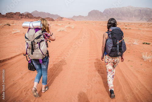 Two young girl are walking across Wadi Rum desert, Jordan