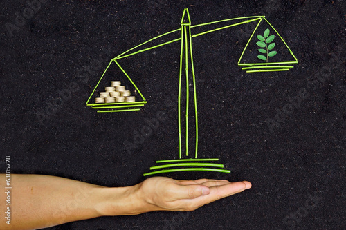 Tree and money to balance scales on soil background / csr