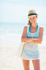 Portrait of happy young woman in hat with bag on beach