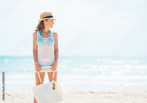 Happy young woman in hat with bag on beach looking on copy space