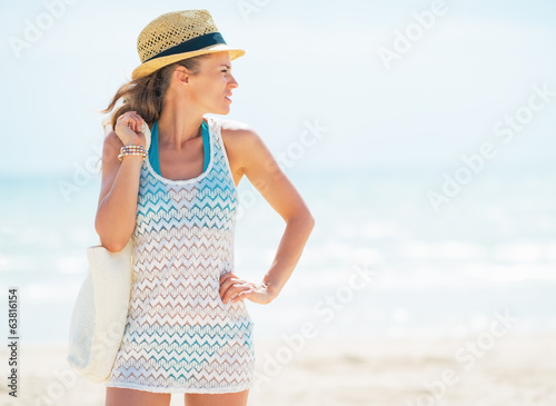 Young woman in hat with bag looking on copy space