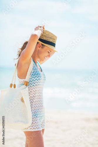 Relaxed young woman in hat with bag on beach